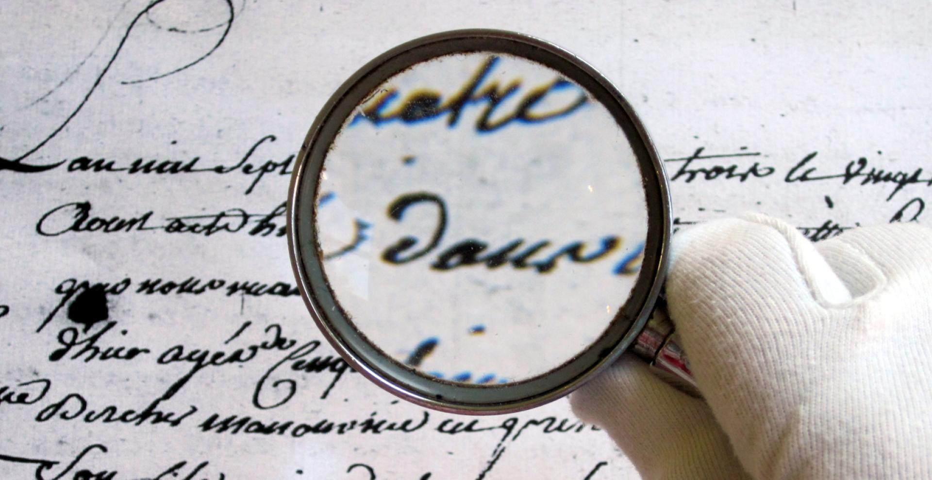 Main tenant une loupe sur un texte ancien, exercice de paléographie