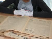 Élève cherchant des informations dans un journal
