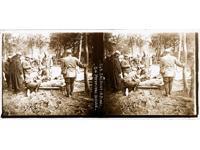 Photographie en forêt de plusieurs soldats entourant un blessé sur une civière.