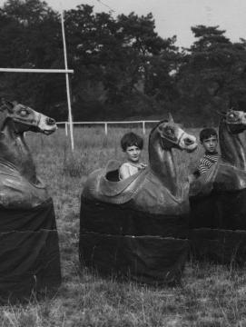 Enfants jouant aux chevaux de bois