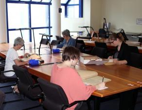 Lecteurs consultant des documents en salle de lecture des Archives