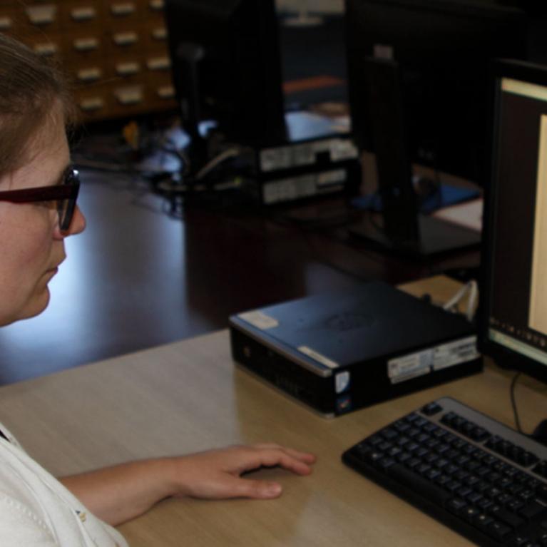 Consultation d'archives sur ordinateur en salle de lecture