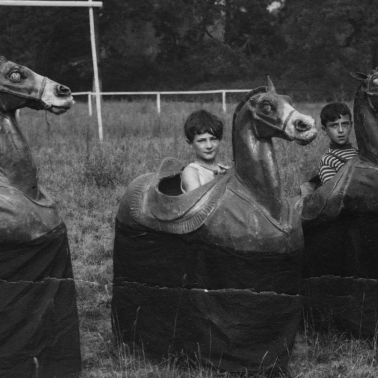 Photographie d'enfants jouant aux chevaux de bois