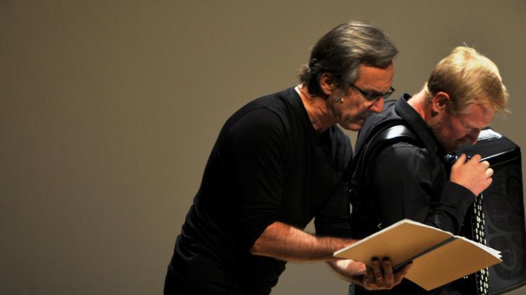 Vue de Marc Roger lisant en compagnie de l'accordéoniste Laurent Derache