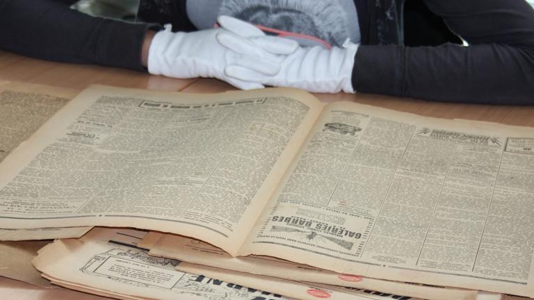 Mains dotées de gants consultant un journal